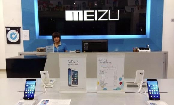 Shop assistant waits for customers at a Meizu store as Meizu MX3 smartphones are seen on display in the foreground, in Shenzhen